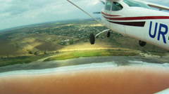 Small plane flies over the red color estuary and the fields - stock footage
