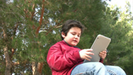 Stock Video Footage of Little boy by himself and using a digital tablet