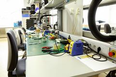 electronics equipment assembly workplace - stock photo