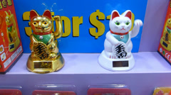 Two maneki-neko (ornament cat) with raising left paws  (MANIKI NEKO--1) Stock Footage
