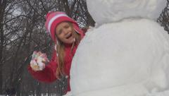 Child, Little Girl Playing Hide and Seek by Snowman in Park, Winter, Children Stock Footage