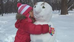 Child Holding, Kissing a Snowman, Little Girl Playing in Park, Winter, Children Stock Footage