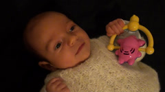 Baby holds toy without interest Stock Footage