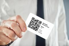 businessman holding qr code business card - stock photo