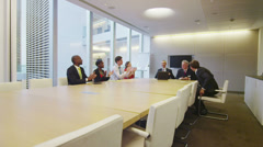 Diverse business team clap and shake hands at the end of a boardroom meeting - stock footage