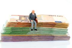 senior sitting on bills - stock photo