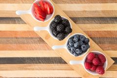 Dishes of fresh berries on decorative striped wood Stock Photos