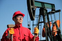 Oil Industry Worker Holding Sledgehammer Next to Pump Jack Stock Photos