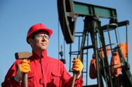 Stock Photo of Oil Industry Worker Holding Sledgehammer Next to Pump Jack