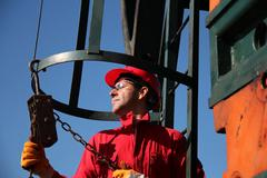Oil Industry Worker Using Chain Winch Stock Photos