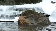 Rock at river bank in winter scenery - stock footage