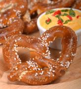 Freshly made german style pretzel with a cheddar cheese spread Stock Photos