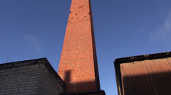 Old red brick chimney and blue sky Stock Footage