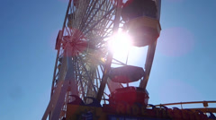 Ferris wheel spinning over the sun Stock Footage