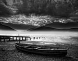 Stock Photo of old boat on lake of shore with misty lake and mountains landscape with stormy