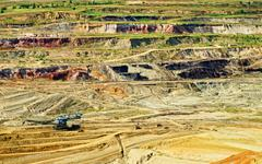 Bunk wall surface mine with exposed colored minerals and brown coal Stock Photos