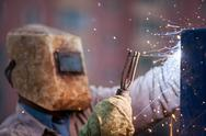 Stock Photo of arc welder worker in protective mask welding metal construction