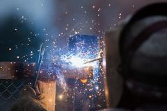 Arc welder worker in protective mask welding metal construction Stock Photos