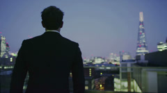Successful businessman looks out at the view of the London city skyline at night - stock footage