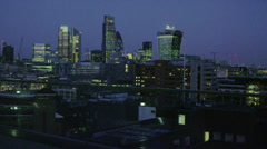 Successful businessman looks out at the view of the London city skyline at night Stock Footage
