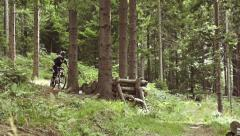 SLOW MOTION: Downhill biker jumping the kicker - stock footage
