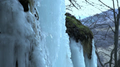 Water runs down the frozen waterfall in the distance trees.Slow motion Stock Footage