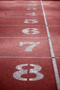 View of a red tartan athletic running track with white numbers Stock Photos