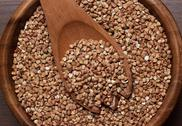 Stock Photo of brown wooden bowl full of buckwheat close-up