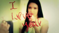 Pretty Girl Erases Lipstick on Mirror I Love You Stock Footage