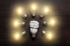Energy saving lamp in comparison with glow lamps concept Stock Photos