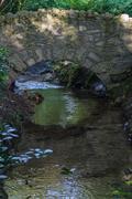 Stone bridge over stream Stock Photos