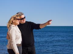 affectionate mature couple at the seaside pointing copyspace - stock photo