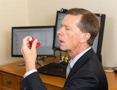 senior businessman with asthma inhaler - stock photo