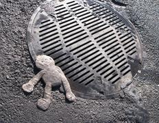 crushed doll on manhole cover - stock photo