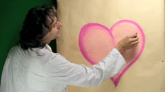 Artist paintings a love symbol Stock Footage