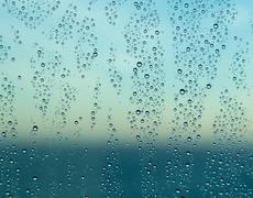 Raindrops on window of a ship at sea with horizon Stock Photos