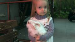 Girl hold in hands and kiss the bunny rabbit. Petting Zoo. Stock Footage