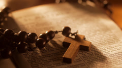 Rack focus from Rosary Beads to title of Gospel of Matthew Stock Footage