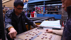 Men play Chinese board game in the street Stock Footage