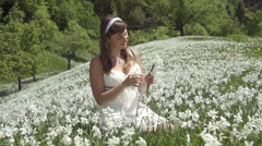 SLOW MOTION: Woman in white dress on a daffodil field Stock Footage