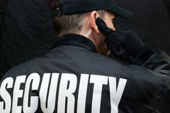 Security guard listens to earpiece, back of jacket showing Stock Photos