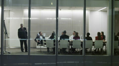 Diverse business team in late night boardroom meeting in contemporary office - stock footage