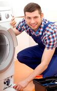 Handyman in blue uniform fixing a washing machine Stock Photos