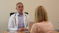 Doctor and patient consultation in Doctors surgery Stock Footage