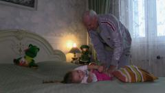 Grand Father Play on the bed with Grand Daughter Stock Footage