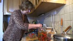 Old Woman Cook tomato at the Kitchen. Slider. - stock footage