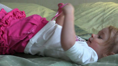 Little girl lying, plays and gets up on the bed. Slider. Stock Footage