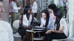 Beautiful mixed ethnicity businesswomen chatting in the office cafe area - stock footage