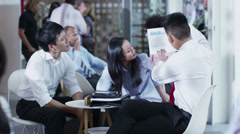 Cheerful Asian business group in informal meeting in office cafe area - stock footage