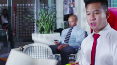 Young businessman sits alone, looking at his phone in office cafe area Stock Footage